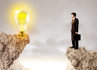 Businessman on rock mountain with idea bulb