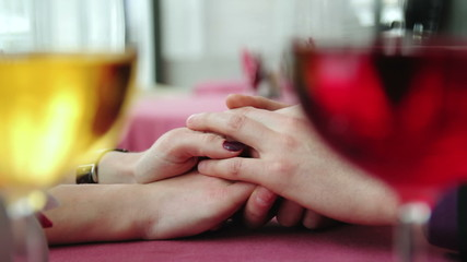 Hands of lovers on a background with wine glasses