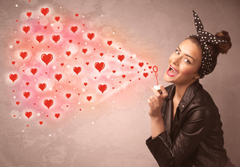 Pretty young girl blowing red heart symbols