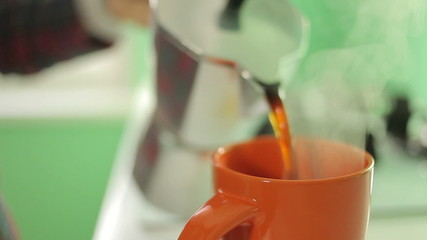 hand pouring coffee into the cup, close-up