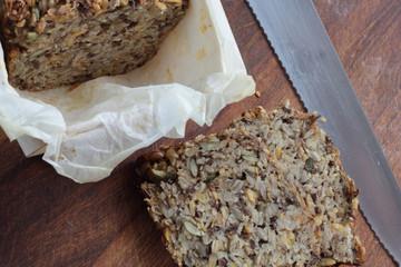 Piece of whole grain bread on wooden board.