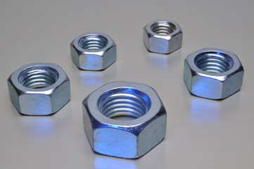 Group of steel nuts with blue light reflection