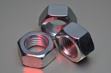 Group of steel nuts with red light reflection