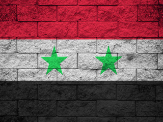 Flag of Syria painted onto a grunge brick wall