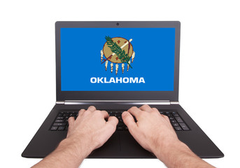 Hands working on laptop, Oklahoma
