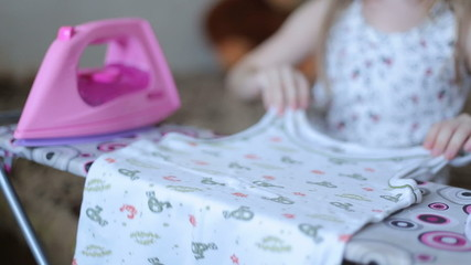 Little girl is ironing clothes with toy iron, close-up