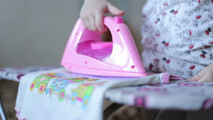 Little girl is ironing clothes with toy iron and folding clothes