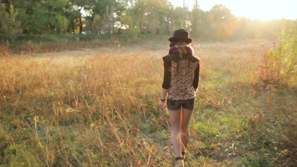 Girl in the hat walking through a meadow