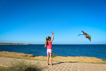 A little girl runs into the sky flying snake by the sea