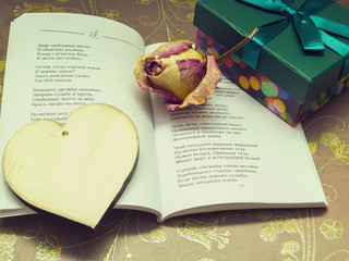 a poem, a wooden heart, dried roses and a box with a gift
