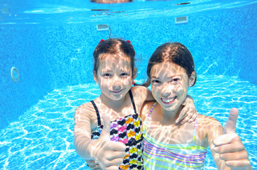 Kids swim in pool underwater, girls swimming and having fun