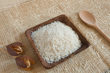 Uncooked Basmati rice in a wooden cup