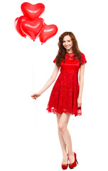 Young woman holding heart-shaped balloons