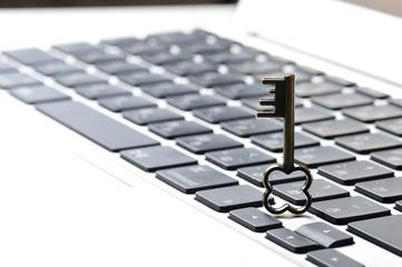 パソコンのキーボードと小さな鍵の写真,個人情報保護のイメージ