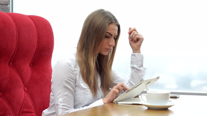 Beautiful young woman sitting in a cafe with tablet.