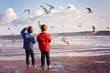 Two adorable kids, feeding the seagulls on the beach - 75842613