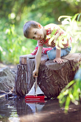 Cute little boy playing on a pond with a toy boat in hands in a