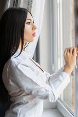 Beautiful woman opens a window