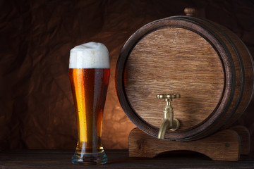 Beer barrel with beer glass on wooden table dark still-life