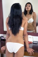 Woman in underwear controls himself in the mirror