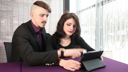 Man and woman looking at the tablet