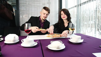 Couple eating pizza in cafe