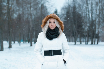 Beautiful girl  in a winter jacket stands in the park