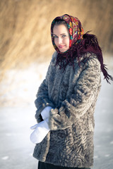 Beautiful Russian girl in national headdress on a winter day