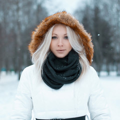 Beautiful girl in a winter jacket in the park