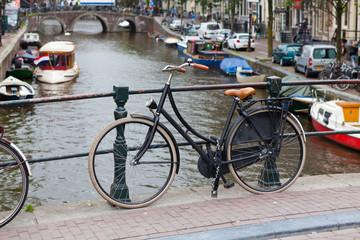 Damenfahrrad vor einer Gracht in Amsterdam
