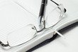 opened business diary with pen and glasses over white background
