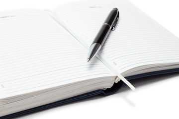 opened business diary with a pen over white background