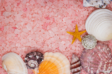 pink bath salt and seashells background