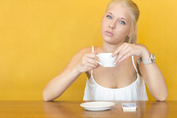 Blonde woman drinks coffee at cafe