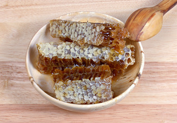 honey comb in a wooden bowl, spoon