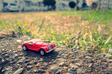 赤色のオープンカーのミニチュアが荒野をドライブする様子