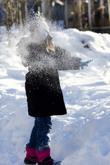 Girl playing with snowball.