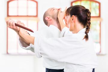 Mann und Frau beim Aikido Messerkampf