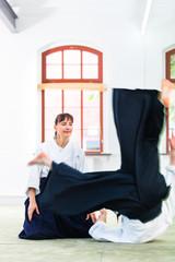 Aikido Lehrer und Schüler trainieren Werfen und Fallen