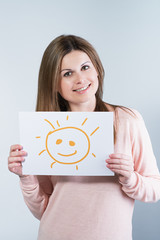 woman holding a cardboard with a sun