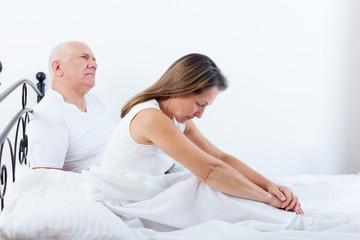 Mature couple having quarrel on   bed