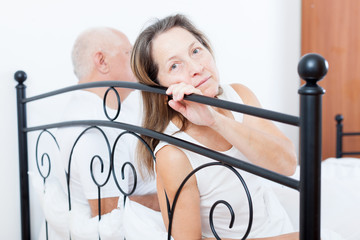 Mature couple having quarrel  in   bedroom.