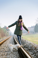 Little girl with dog walking on the railroad