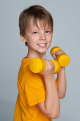 Cute young boy with dumbbells do exercises