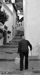 Elderly man climbs the stairs of a street in a town