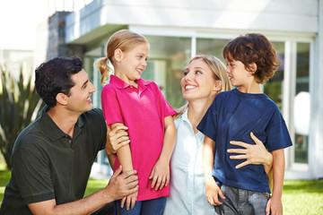 Lachende Familie im Garten vor dem Haus