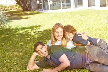 Lachende Familie liegt im Garten vor Haus