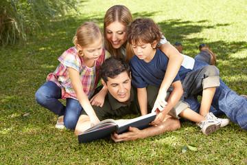 Familie beim Lesen vom Buch im Garten