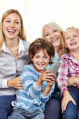 Familie mit Fernbedienung schaut Fernsehen im Wohnzimmer