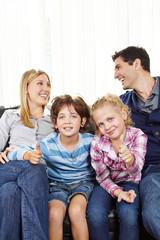 Geschwister halten Daumen hoch zwischen Eltern